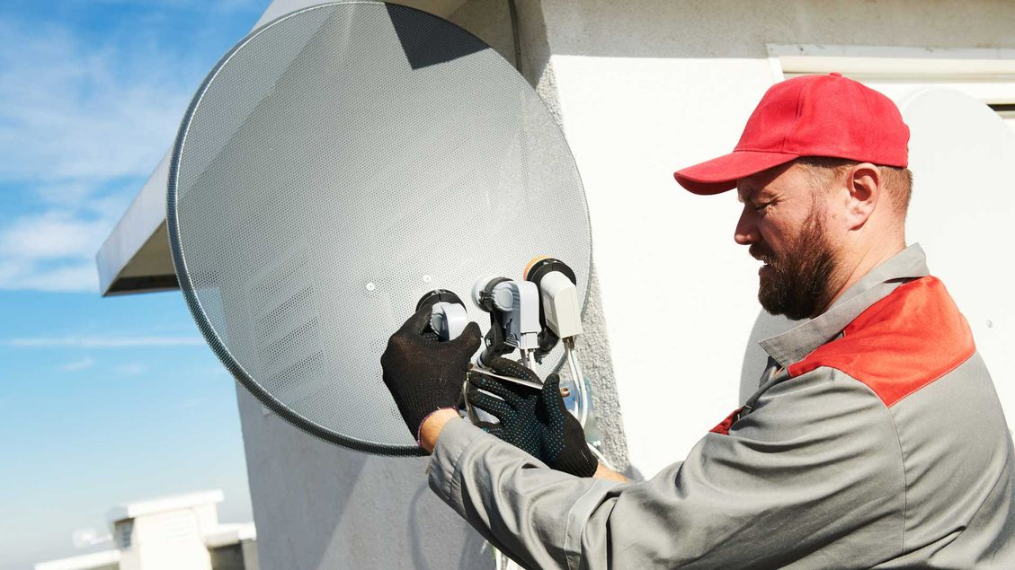 A professional installing a satellite antenna